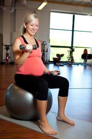 A pregnant woman doing bicep muscle exercises using dumbbells while seated on a fitness ball Stock Photo