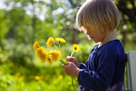 Little girl outdoors on a summer day with dandelions Stock Photo