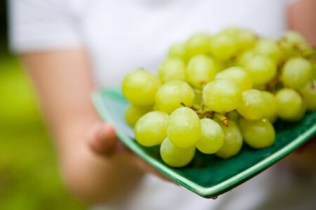 Beautiful fresh green grapes on a plate held by womans hands 스톡 콘텐츠