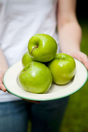 Close-up of beautiful, juicy green apples on a plate held by a woman