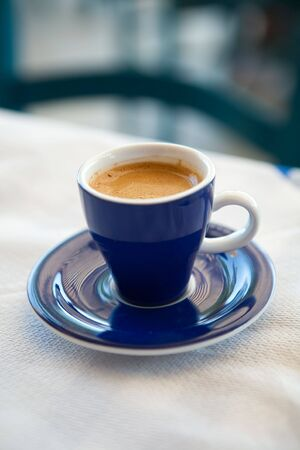 Cup of delicious fresh greek coffee on an outdoor cafe table photo