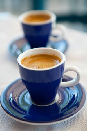 Two cups of delicious fresh greek coffee on an outdoor cafe table