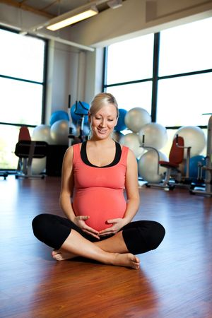 A pregnant woman smiling and relaxing in a gym while holding her belly. photo