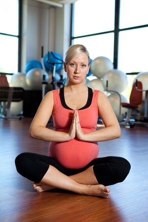 A pregnant women relaxing in a sitting position in a health and fitness gym. photo