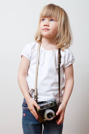 Little girl with an old camera. Studio shot. photo