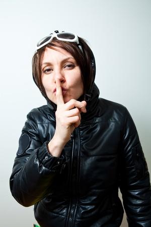 shush: Young trendy woman gesturing shush. Studio shot.