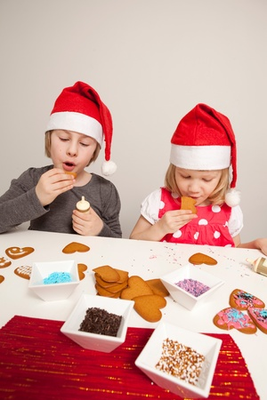 Girls decorating gingerbread cookies at Christmas. Studio shot. photo