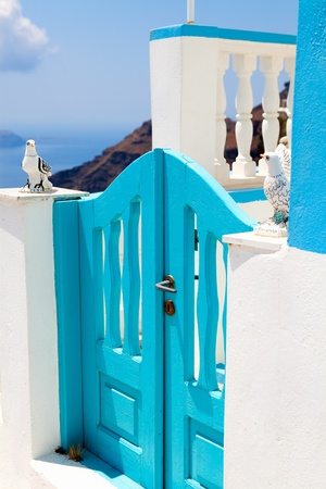 fira: Old turquoise colored wooden gate in Thira, Santorini, Greece