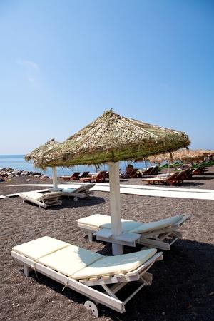 sunshades: Beach umbrellas and sunbeds in morning sun in Perissa beach, Santorini, Greece