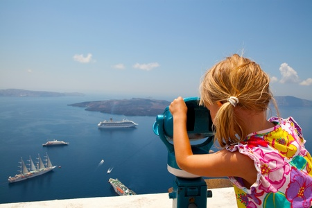 thira: Girl looking at cruise ships with binoculars in Thira, Santorini, Greece