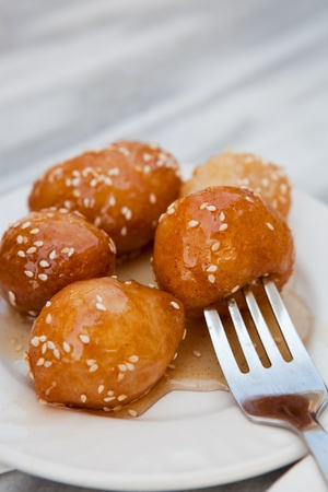Loukoumades, a greek dessert, served on a white plate with honey