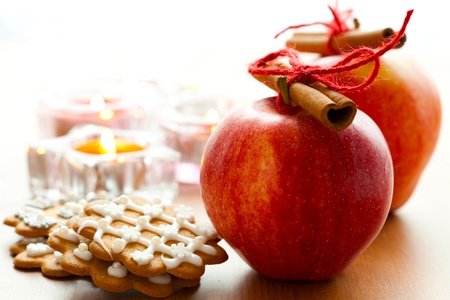 Close-up of delicious red Christmas apples with cinnamon sticks, gingerbread cookies and candles Stock Photo