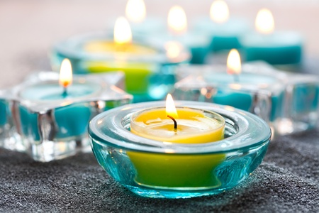 Close-up of blue and yellow Christmas candles on silver sand Stock Photo