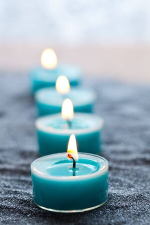 Close-up of blue candles on silver sand Stock Photo