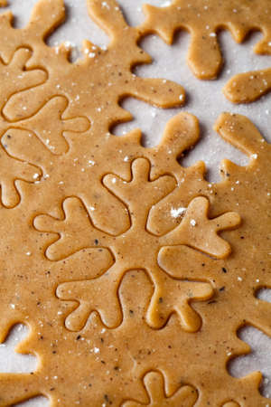 Making gingerbread cookies for Christmas. Gingerbread dough with snowflake shapes. photo