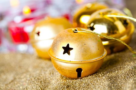Close-up of golden jingle bell Christmas baubles with candles photo