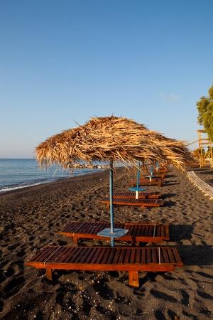 sunbeds: Beach umbrellas and sunbeds at sunrise in Perissa beach, Santorini, Greece