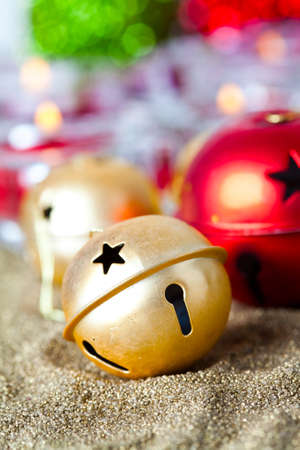 Close-up of golden and red jingle bell Christmas baubles with candles