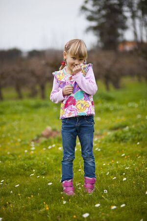 Cute little girl standing on a green field with flowers Stock Photo - 12027597