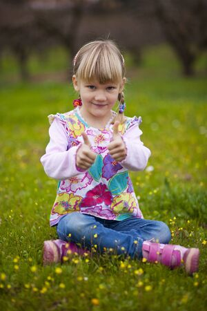 Cute little girl outdoors on a green field with thumbs up photo