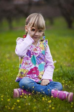 Cute little girl outdoors looking through imaginary binoculars photo