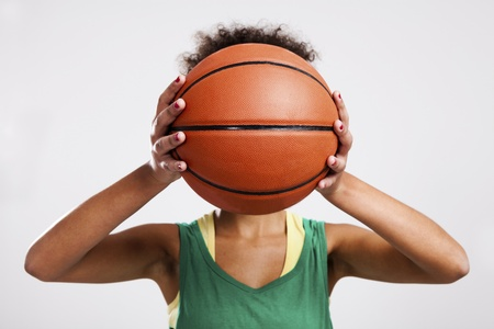 Athletic woman with a basketball in front of her face. Studio shot. photo