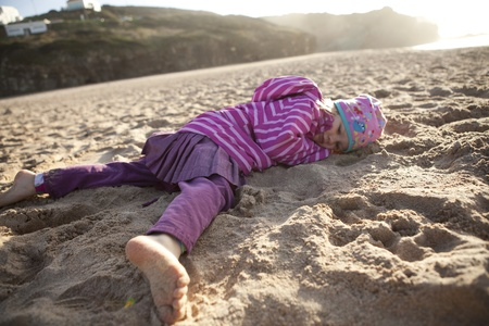 Cute little girl lying in sand on the beach photo