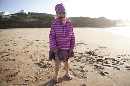 little girl barefoot: Portrait of a cute little girl standing barefoot on the beach