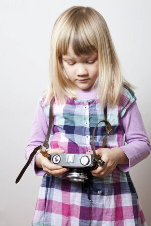 Little girl with a vintage camera. Studio shot. photo