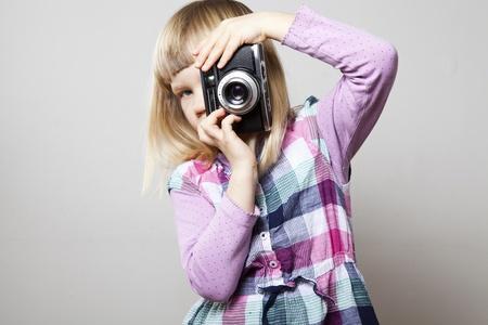 Little girl with a vintage camera. Studio shot.
