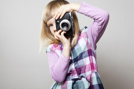 Little girl with a vintage camera. Studio shot. Stock Photo - 12649474