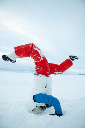headstand: Woman doing yoga and a headstand in snow on a white winter day Stock Photo