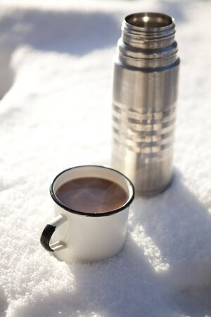 Mug and thermos of hot chocolate on a cold winter day in snow photo