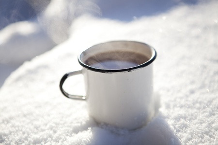 Mug of hot chocolate outdoors on a winter day in snow