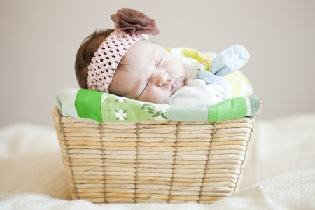 Portrait of a cute newborn baby girl sleeping in a basket photo