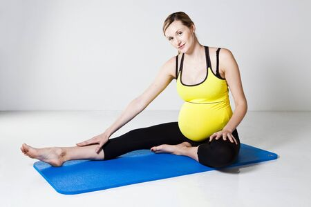hamstring: Pregnant woman sitting on a mat and performing a hamstring muscle stretch of the leg Stock Photo