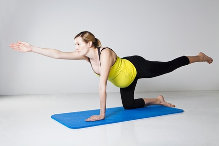 Pregnant woman exercising on mat to develop balance and muscular strength of the core trunk and shoulder muscles Stock Photo