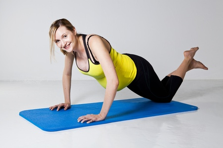 strengthening: Pregnant woman doing a chest muscle strengthening push-up exercise on a mat