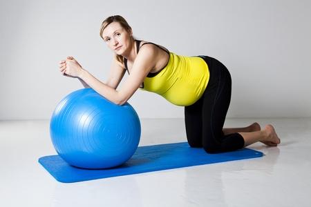 укрепление: Pregnant woman doing an abdominal core strengthening exercise using a fitness ball on a mat Фото со стока