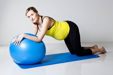 strengthening: Pregnant woman doing an abdominal core strengthening exercise using a fitness ball on a mat Stock Photo