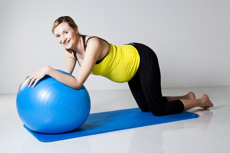 Pregnant woman doing an abdominal core strengthening exercise using a fitness ball on a mat Stock Photo - 12884387