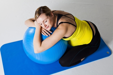 Pregnant woman relaxing while leaning against a fitness ball on a mat Stock Photo - 12884511
