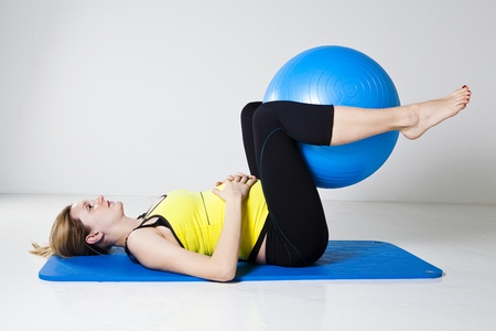 Pregnant woman performing an abdominal strengthening exercise using a fitness ball while lying on a mat