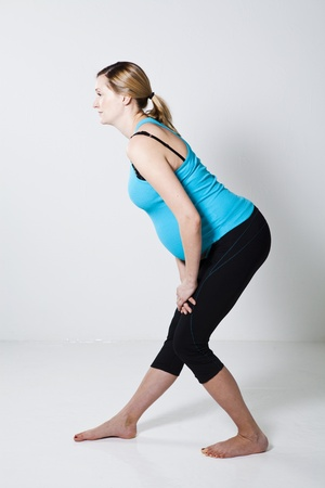 hamstring: Pregnant woman performing a leg stretching exercise for the hamstring muscles