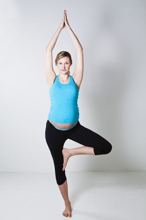 Pregnant woman doing a yoga stretching and balance exercise photo