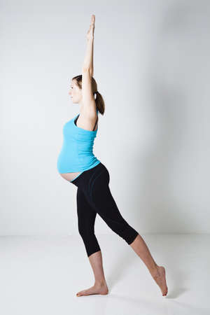arms above head: Pregnant woman doing a yoga stretching and balance exercise with arms above head Stock Photo
