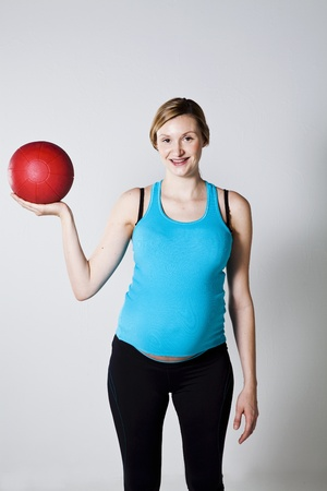 Pregnant woman exercising with a red exercise ball Stock Photo - 12970249