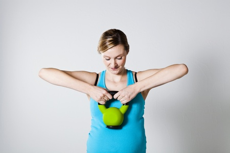 Pregnant woman doing shoulder muscle strengthening exercise with kettlebell Stock Photo - 12970167