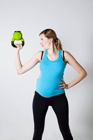 Pregnant woman doing exercises with kettlebell photo