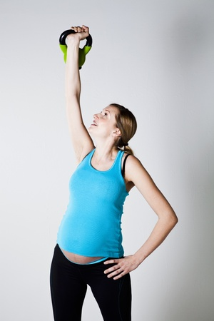 Pregnant woman doing shoulder muscle strengthening exercise with kettlebell Stock Photo - 12970239